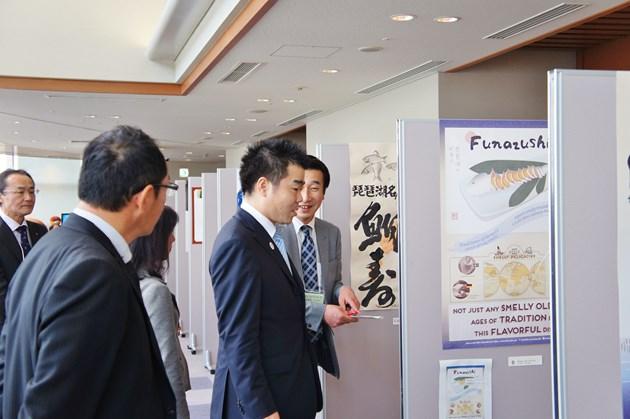 滋賀名産ふなずしをテーマに各クリエーターがデザインしたポスターを見て回る三日月滋賀県知事。